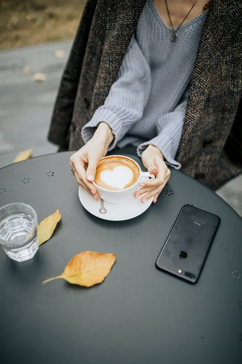 A Person Holding a Cup of Coffee on Black Table