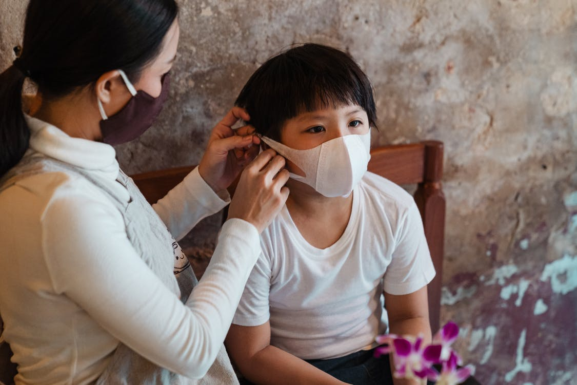 Caring woman putting face mask on son