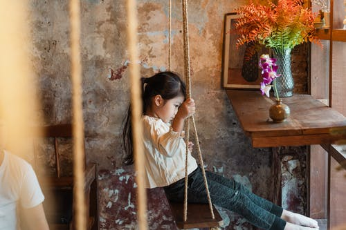Photo of Girl Sitting on Wooden Swing
