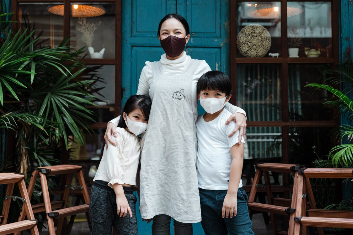 Optimistic Asian woman embracing adorable son and daughter wearing casual clothes and medical protective masks while standing against rural weathered building and plants