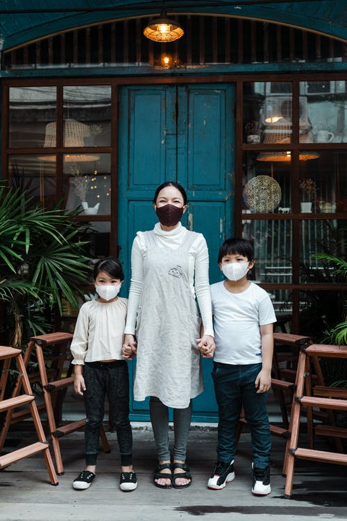 Calm woman with son and daughter in face masks