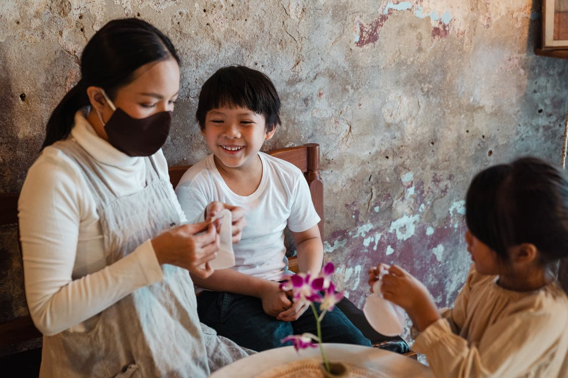 Optimistic Asian mother in face mask putting respirators on smiling son and daughter while spending time together in rural house against shabby wall