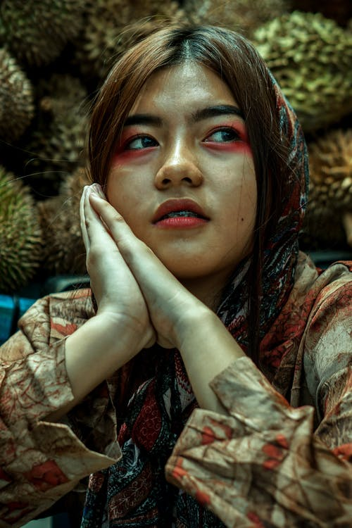 Calm young Asian lady with clasped hands sitting against pile of exotic fruits and looking away