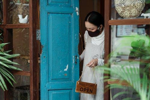 Calm woman in respirator with open sign near shop door