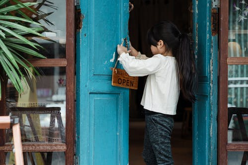 Photo of Girl Putting Wooden Signage on Doorknob