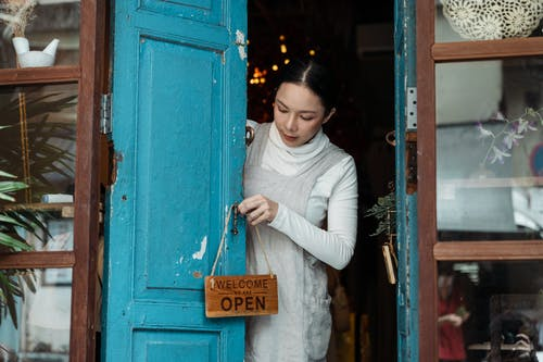 Photo of Woman Putting Wooden Signage on Doorknob