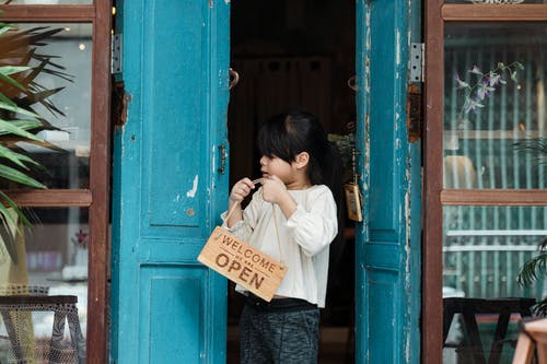 Photo of Girl Holding Wooden Welcome Signage While Standing on Doorway