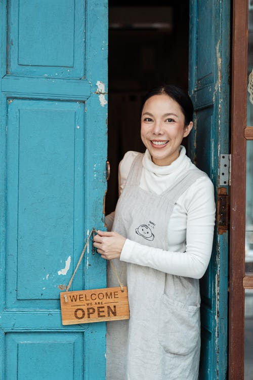 Photo of Woman Smiling While Holding Wooden Signage