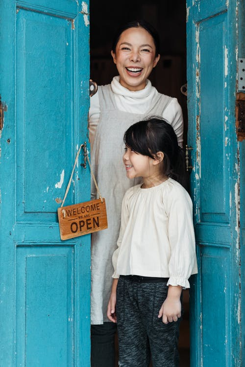 Photo of Woman and Girl Standing on Doorway