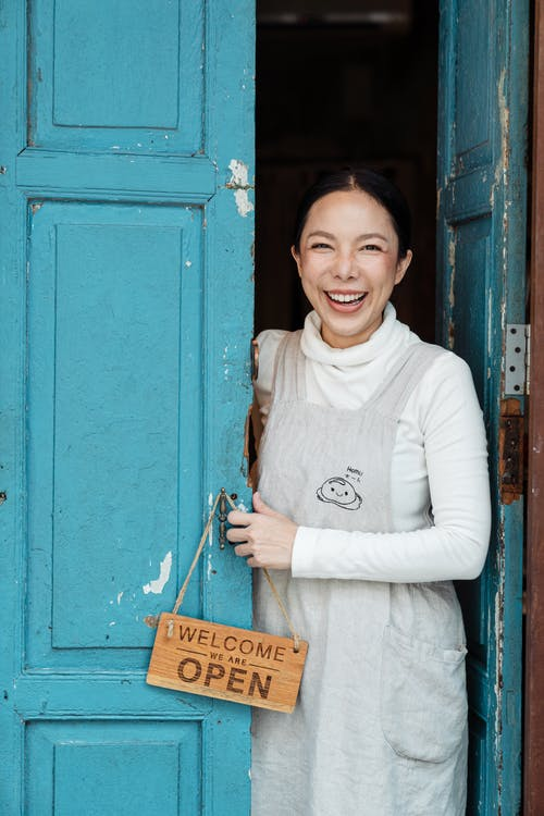 Photo of Woman Smiling While Standing on Doorway
