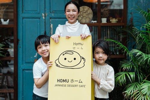 Photo of Family Smiling While Holding Signage