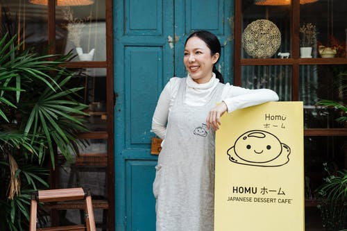 Photo of Woman Smiling While Leaning on Signage