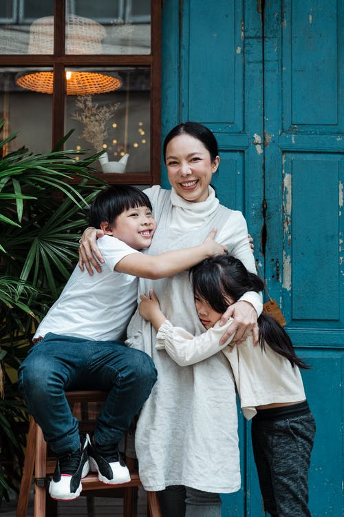 Photo of Woman Hugging Her Children While Smiling