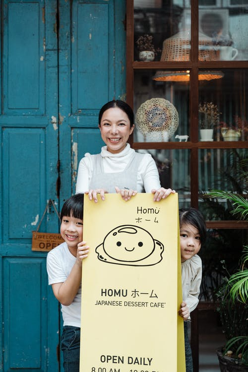 Photo of Family Smiling While Standing Near Signage