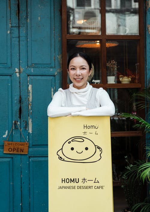 Woman Smiling While Leaning on Signage