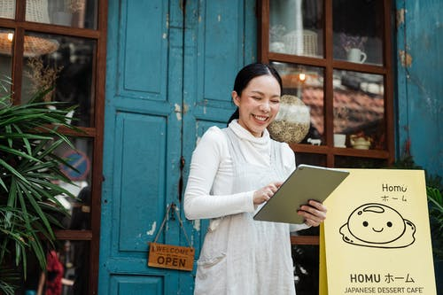 Cheerful woman with clipboard near cafe entrance