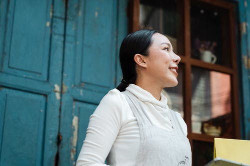Happy smiling Asian female in apron standing against blue shabby weathered building and looking away dreamily