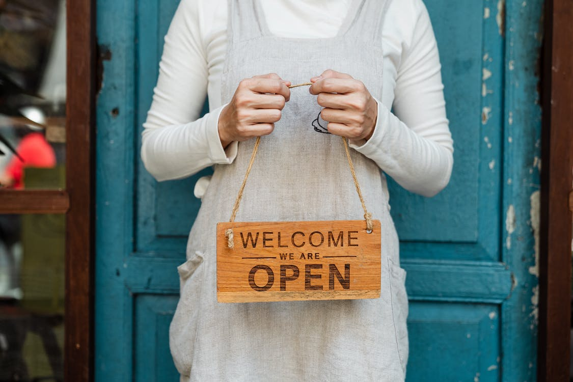 Person Holding Brown Wooden Welcome Signage