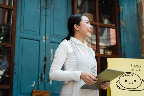 Woman in White Long Sleeve Shirt Holding Brown Box
