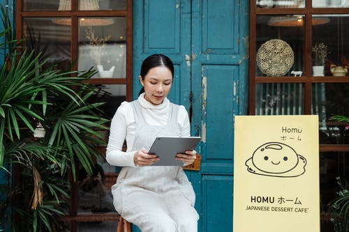 Content woman with modern tablet near cafe entrance