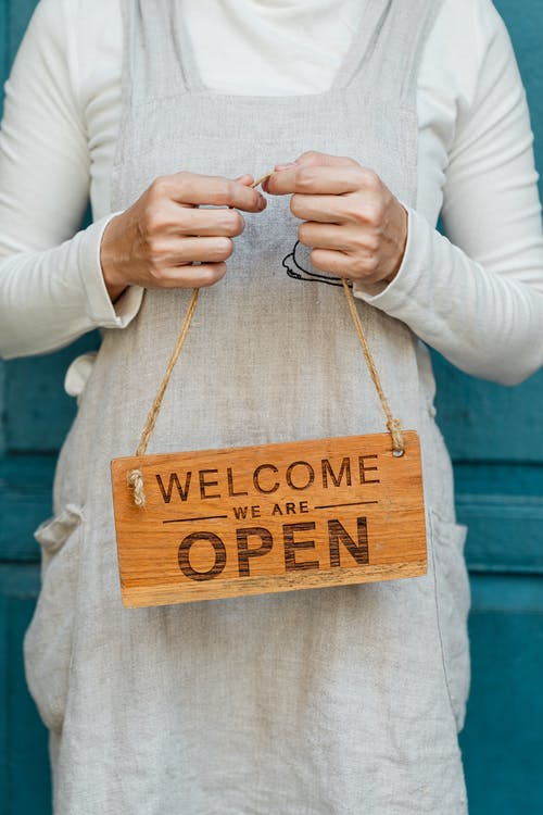 Crop faceless female in casual clothes and apron demonstrating wooden sign with text welcome we are open against blue door