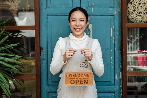 Cheerful ethnic female cafeteria owner in apron demonstrating cardboard signboard while standing near blue shabby door and windows after starting own business and looking at camera