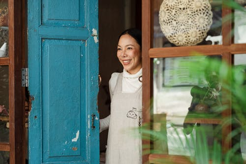 Photo of Woman Smiling While Standing on Wooden Doorway