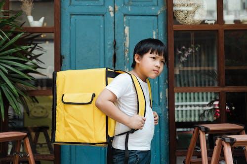 Ethnic boy with heavy food backpack near shabby entrance door