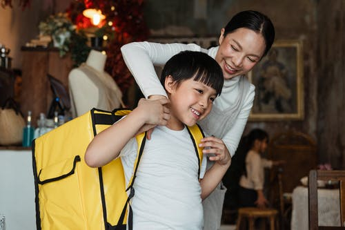 Happy female cafeteria employee putting on big yellow thermo bag on shoulders of positive child in casual wear working as food courier and looking away
