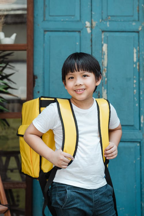 Happy ethnic boy carrying food backpack