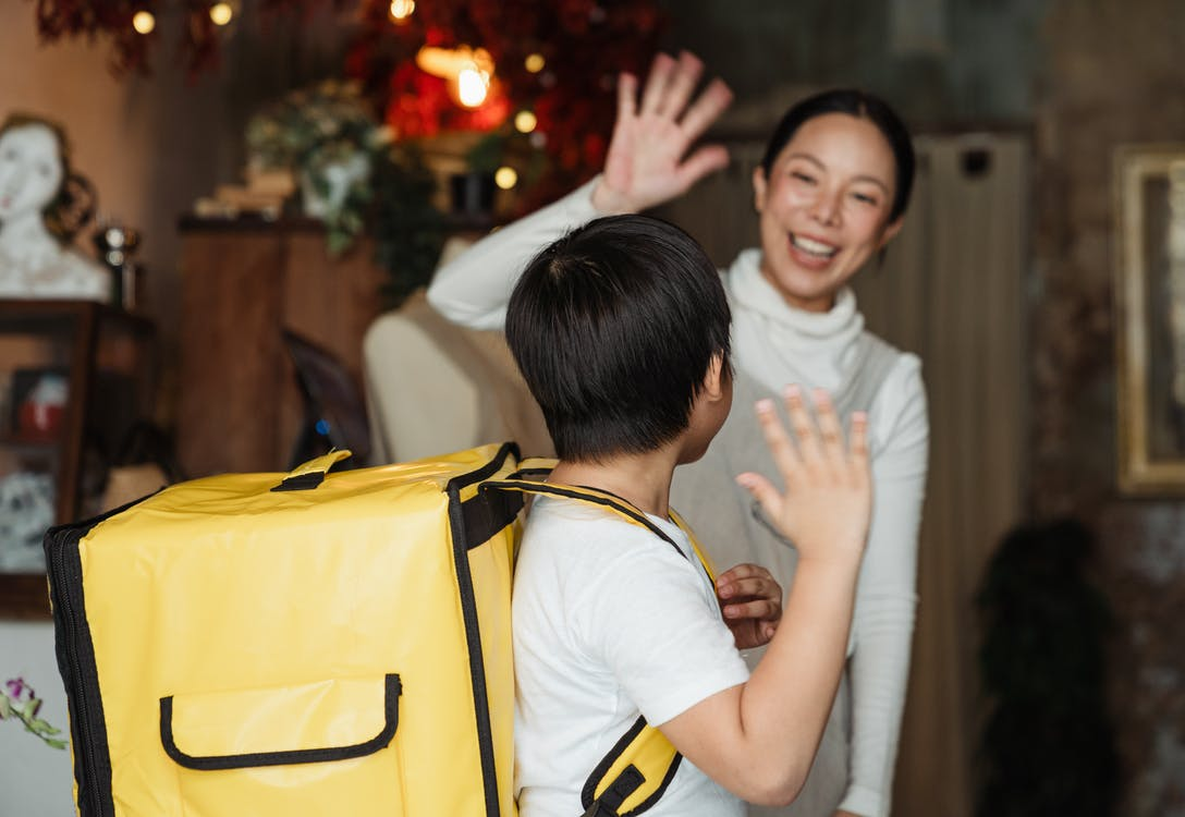 Happy ethnic female cafe worker in apron wishing farewell to boy with food delivery backpack helping in family business