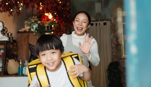 Cheerful ethnic mother saying goodbye to son with food backpack