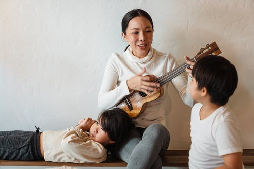 Cheerful slim female musician playing acoustic ukulele while sitting with crossed legs in apartment near charming sons in casual wear
