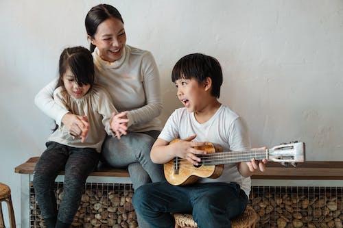 Ethnic boy playing ukulele while sitting with mother and sister