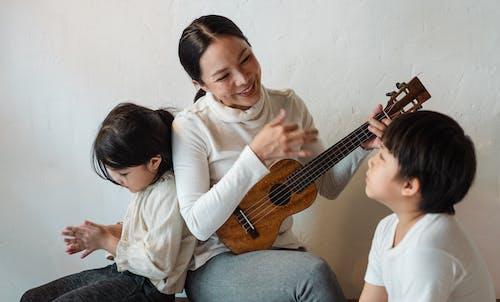 Smiling ethnic female playing ukulele while sitting with children