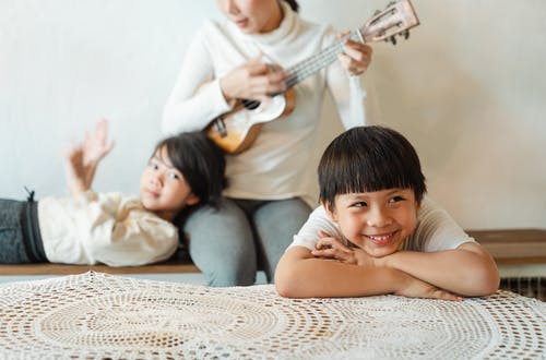 Crop anonymous woman playing ukulele while entertaining ethnic children