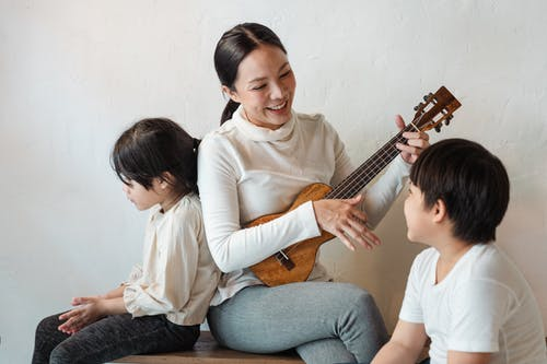 Positive ethnic mother playing ukulele for siblings in house