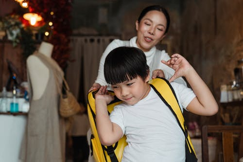 Positive ethnic mother helping son to wear delivery backpack