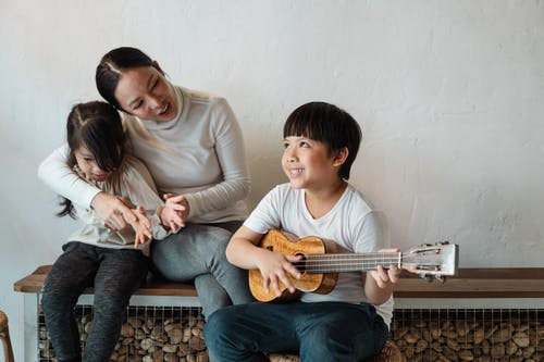 Dreamy ethnic brother in casual wear playing Hawaiian musical instrument while looking up and sitting near little sister and mother on wooden bench