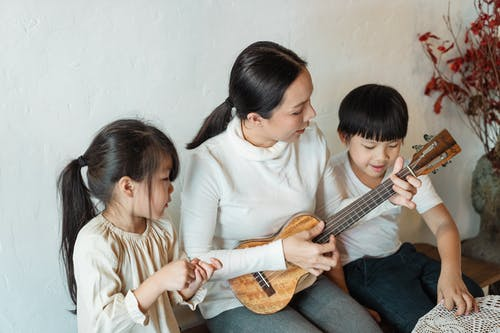 Female musician playing musical instrument for ethnic children at home