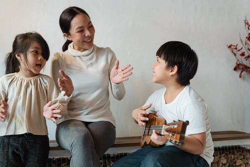 Happy ethnic mother and daughter clapping hands and singing song while positive son playing Hawaiian musical instrument at home