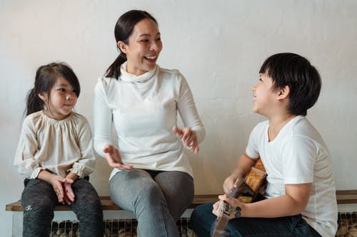 Ethnic child playing ukulele and mother with daughter clapping hands