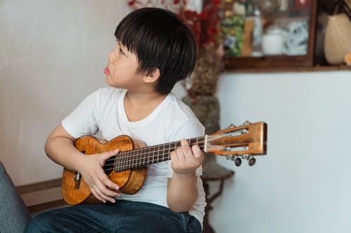 Ethnic child making grimace while playing Hawaiian ukulele in house