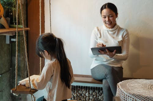 Ethnic mother using tablet while faceless daughter drawing on paper