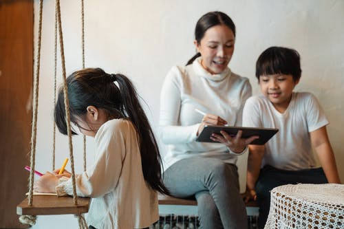 Ethnic mother surfing internet on tablet spending time with children