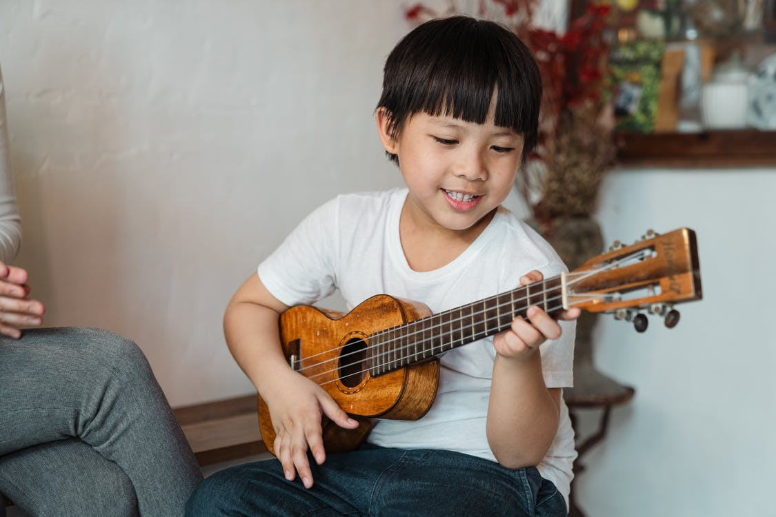 Content ethnic child in casual wear playing traditional Hawaiian musical instrument while sitting near crop faceless person at home in daylight