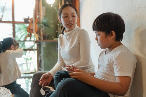 Positive ethnic woman sitting near cute son using tablet against adorable daughter looking at window while spending free time together at home