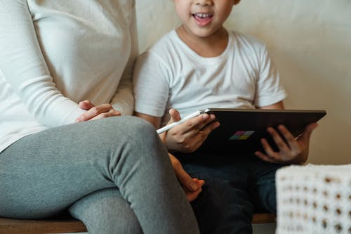Unrecognizable woman with son using tablet at home