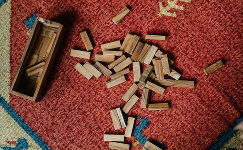 Top view of wooden box and pile of blocks for playing in jenga tower game arranged on floor carpet