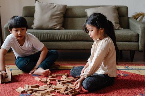 Adorable ethnic kids playing jenga at home on floor